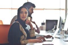 De multiraciale eigentijdse bedrijfsmensen die verbonden aan technologische apparaten zoals tablet en laptop werken stock foto's