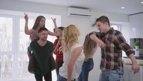 De multiraciale groep die vriendenpret met plastic koppen in hun danst dient grote moderne flat bij een huispartij in stock video