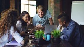 De multiraciale groep medewerkers spreekt en het lachen zitting bij bureau in bureau van succesvol bedrijf De jongeren bent stock videobeelden