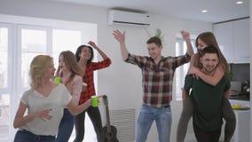 De multiraciale groep vrienden die partij hebben thuis, de jeugd heeft pret en danst met plastic koppen in handen stock video