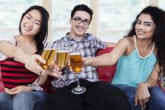 De multiraciale tieners roosteren met bier Stock Fotografie