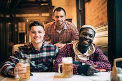 De multiraciale vrienden groeperen drinkend en roosterend bier bij bar Vriendschapsconcept met jongeren die van tijd samen en hav royalty-vrije stock foto's