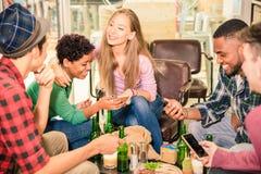 De multiraciale vrienden groeperen samen het drinken bier en het hebben van pret stock fotografie
