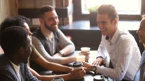 De multiraciale vrienden sluiten zich aan bij handen die samen hoog-vijf geven op coffeehouse vergadering stock video