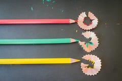 De multispaanders van kleurenpotloden op donkere achtergrond Stock Afbeeldingen