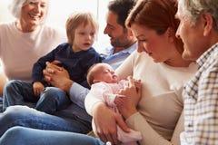 De multizitting van de Generatiefamilie op Sofa With Newborn Baby Stock Fotografie
