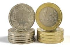 De munt van de euro en van de frank Stock Afbeeldingen