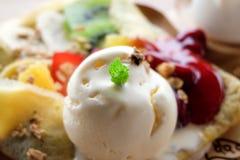 De muntbladeren op smeltend vanilleroomijs met fruit omfloersen, selectieve nadruk op kleine muntbladeren Stock Foto