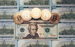 De muntstukken bitcoin, het geld ligt, op de rekeningslijst van 20 dollars De bankbiljetten worden uitgespreid op de lijst in een Stock Fotografie