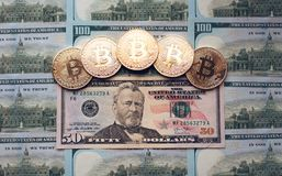 De muntstukken bitcoin, het geld ligt, op de rekeningslijst van 50 dollars De bankbiljetten worden uitgespreid op de lijst in een Stock Foto's