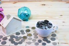 de muntstukken in duidelijke piggy op de houten lijst en heeft rond een hous stock foto's