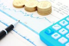 De muntstukken en de grafiek van de pen Stock Foto's