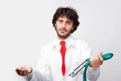 De muntstukken en de stethoscoop van de doktersholding stock afbeeldingen