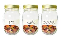 De muntstukken in fles met Belastingsbesparing schenken planetiket op witte backg Stock Foto's