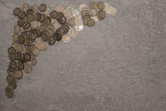 De muntstukken twee euro liggen op de grijze steenachtergrond Munt van de Europese Unie Grote stapel van euro muntstukkenachtergr stock foto