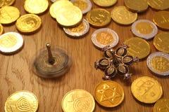 De muntstukken van de Chanoeka gelt chocolade met ster van David bij het achter en zilveren spinnen dreidel met granaatappel royalty-vrije stock afbeeldingen