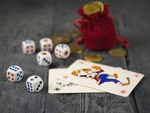 De muntstukken van een zak en een rood worden gegoten dobbelen op een houten zwarte lijst die Stock Foto's