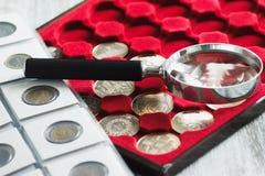 De muntstukken van de verschillende collector in de doos en een vergrootglas stock fotografie