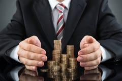 De Muntstukken van zakenmansaving pile of stock fotografie