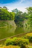 De Muren van de het Kasteelborstwering van Nagoya over Grachtbewolking stock afbeeldingen