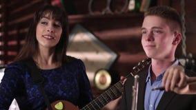 De musici spelen instrumenten Een jonge mens met een fluit in zijn handen neigt zijn hoofd aan de muziek Een mooi meisje in een b stock videobeelden
