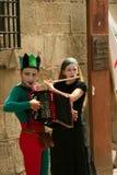 De musici van de straat in harlekijnkostuums. Stock Foto