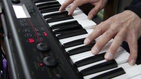 De musicus die de elektrische piano spelen, duwt op de sleutels, stock footage
