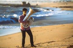 De musicus die de Tuba op de Oceaankust spelen ontspant stock afbeelding