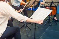 De musicus draait de pagina van Muzieknotitieboekje op tribune met achtergrond van speelcellisten en violistenband op gebeurtenis stock afbeelding
