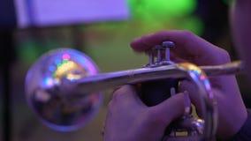 De musicus speelt de trompet in de concertzaal Muzikaal instrumentenclose-up stock footage