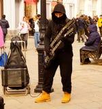 De musicus speelt de gitaar, creeert een culturele atmosfeer viering op de straat Een straatmusicus is een beroeps, of stock afbeelding