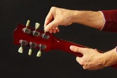 De musicus stemt de gitaar op donkere achtergrond stock foto