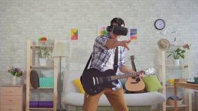 De musicus van de portret jonge mens in VR-glazen die emotioneel de elektrische gitaar spelen stock videobeelden