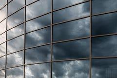 De muur van de glaswolkenkrabber met bezinning van donkere stormachtige wolken bij s Stock Foto's
