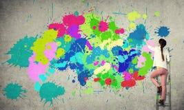De muur van de meisjesverf in kleuren stock fotografie