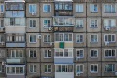 De muur van een dilapidated huis met vensters en balkons royalty-vrije stock afbeelding