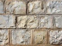 De muur van grote stenen van gele die tonen, met cement in natuurlijk licht worden versterkt stock fotografie