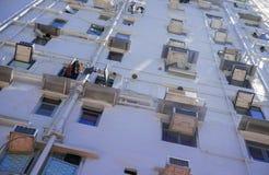 De muur van het gebouw met meerdere verdiepingen met vensters en veredelingsmiddelen stak met stralen van de zon aan royalty-vrije stock foto's