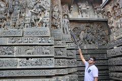 De muur van de Hoysaleswaratempel met een beeldhouwwerk wordt gesneden die als vreemdeling kijken die stock foto's