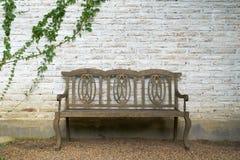 De muur wordt gemaakt van baksteen dan als witte en oude houten voorzitter geschilderd Er zijn klimplanten op de linkermuur Deze  Stock Afbeelding