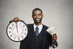 De muurklok en contant geld van de zakenmanholding in handen De tijd is geld Stock Afbeeldingen