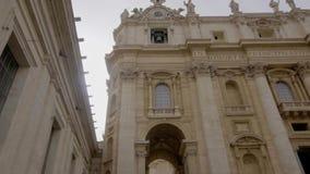 De muurklok en de klokketoren in Basiliek van Heilige Peter in Vatikaan Rome Italië met de grote standbeelden aan de kant van stock videobeelden
