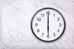 De muurklok toont zes uur op witte marmeren textuur De bureauklok toont 6pm of 6am stock afbeeldingen