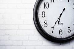 De muurklok wordt gehangen op een witte bakstenen muur, nauwkeurig vertellend de tijd royalty-vrije stock fotografie