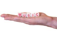 De muziek die met houten wordt geschreven dobbelt op een hand, die op witte achtergrond wordt geïsoleerd stock fotografie