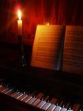 De muziek van de piano en van het blad in het licht van kaars Royalty-vrije Stock Afbeeldingen