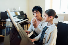 De muziekleraar verklaart ingewikkeldheden van het spelen piano Royalty-vrije Stock Afbeeldingen