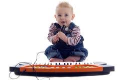 De muzikale baby speelt het toetsenbord en zingt karoke Royalty-vrije Stock Afbeelding