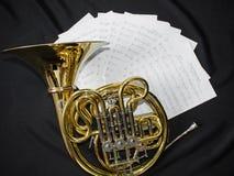De muzikale instrumenten Franse hoorn ligt op een zwarte achtergrond met nota's royalty-vrije stock foto