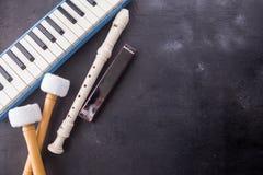 De muzikale instrumentenachtergrond met fluit, pianika, de harmonika, en de baarzen plakken op zwarte houten stock foto